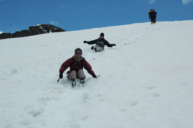 Shari and Lisa glissading down a snow field