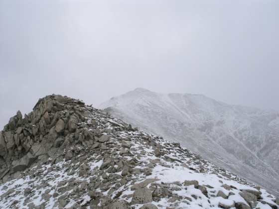 The storm envelopes us and the summit