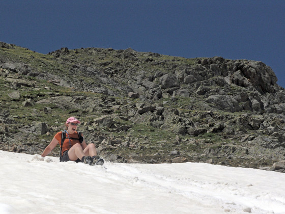 Lisa, glissading down a lengthy snow field to save time on the descent