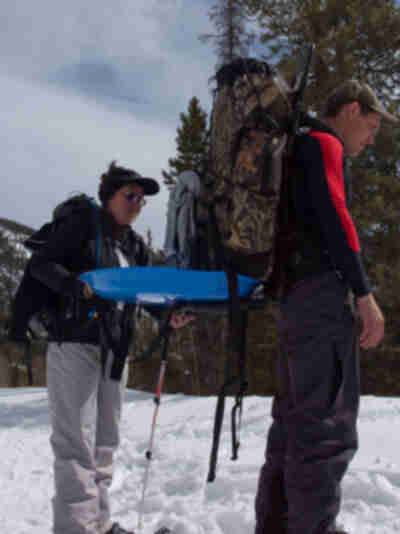 Joy attempts to stow Brian's sled for the steep section of trail...