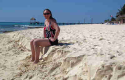 Lisa sits on the eroded sand shelf of the beach